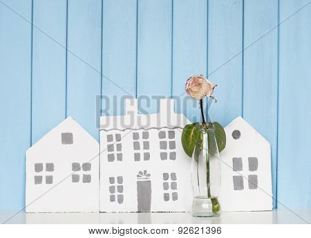 Three Wooden Houses And  White Rose On The Bookshelf