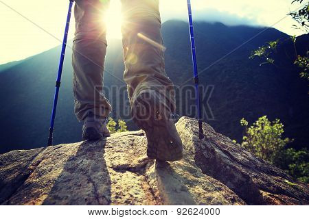 woman hiker legs climbing on sunrise mountain peak rock