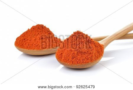 Wooden Spoon Covered With The Red Chili Paprika Powder On White Background