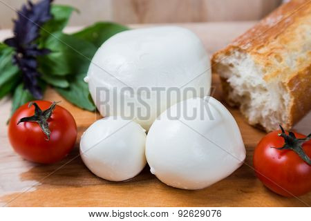 Balls Mozzarella Different Size With Tomatoes Cherry, Bread And Basil On Wood Background