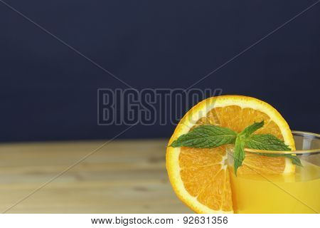 Homemade orange juice garnished with a mint leaf, a view of sliced orange in the glass.
