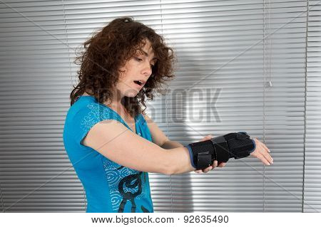Woman In Casual Clothes Looking At Her Arm
