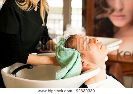 Female Hairdresser Washing Hair Of Smiling Man Client At Beauty Parlour