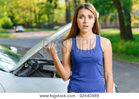Girl pointing on car with opened bonnet
