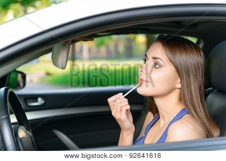 Woman doing makeup inside car