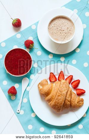 Traditional croissant French sweet dessert with a cup of coffee, fresh strawberry and jam on provenc