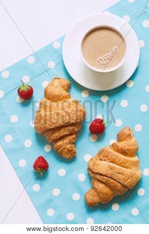Croissant traditional viennoiserie pastry dessert with a cup of coffe and fresh strawberry on proven