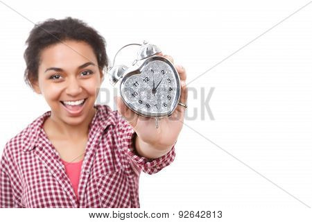 Smiling mulatto girl showing alarm clock
