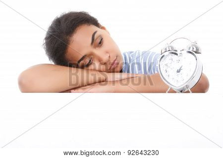 Mulatto girl leaning and looking at alarm clock