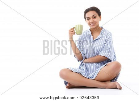 Pleasant young woman sitting with cup