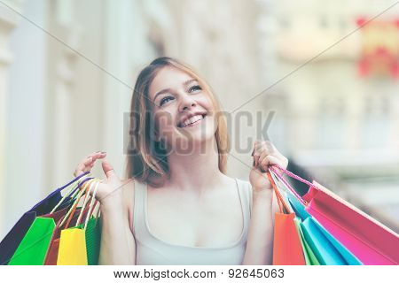 A Happy Young Girl With The Colourful Shopping Bags From The Fancy Shops. Toned Image.