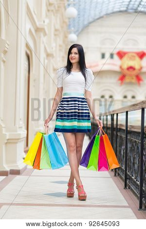 Full-length Happy Smiling Lady With A Lot Of Colourful Shopping Bags From The Fancy Shops. Luxury Sh