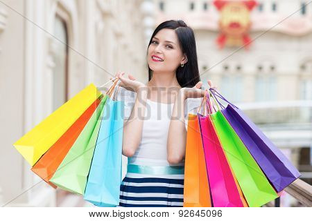 A Happy Smiling Lady With A Lot Of Colourful Shopping Bags From The Fancy Shops. Luxury Shopping Ven