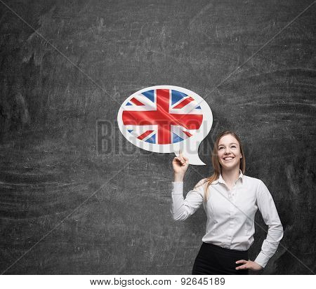 Beautiful Woman Is Pointing Out The Thought Bubble With Great Britain Flag. Dark Background.