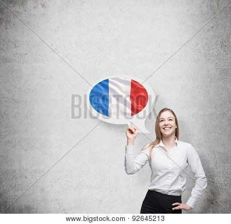 Beautiful Woman Is Pointing Out The Thought Bubble With French Flag. Concrete Background.