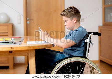 Boy In Wheelchair Doing Homework And Using Tablet Pc