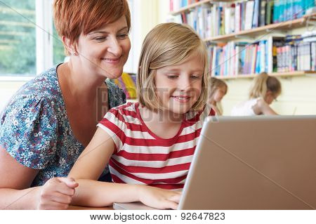 School Pupil With Teacher Using Laptop Computer In Classroom