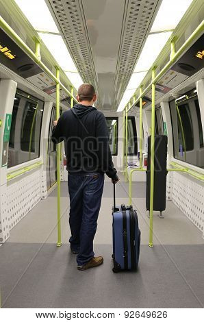 Man with Suitcase on an empty airport train.