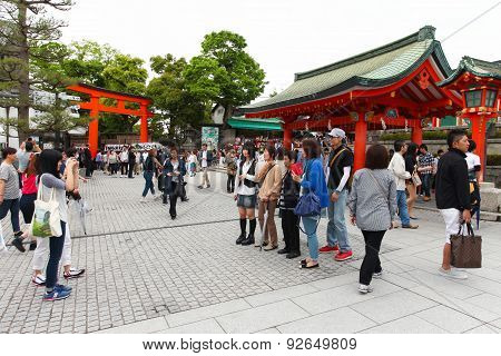 Japanese people and tourists enter Fushimi Inari Shrine in Kyoto
