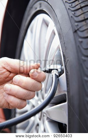 Close Up Of Man Inflating Car Tyre With Air Pressure Line