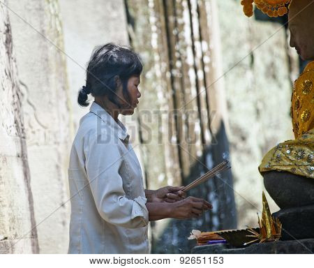 SIEM REAP, CAMBODIA - NOVEMBER 16, 2011: An unidentified woman prays in a Buddhist merit making ceremony at Angkor Wat. Theravada Buddhism is practiced by over 95% of Cambodians.