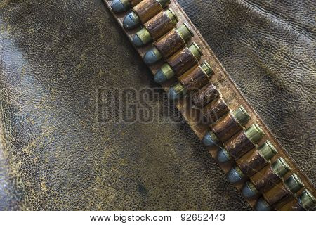 Western Style Leather Gun Belt and Bullets with a Leather background