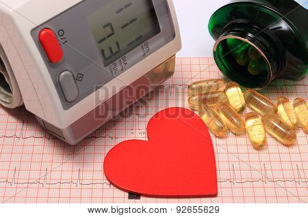Heart Shape, Blood Pressure Monitor And Tablets On Electrocardiogram