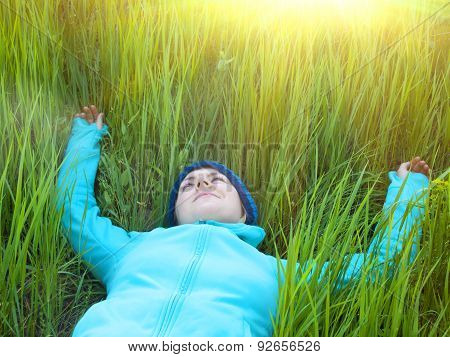 Young Girl Lying In Green Grass.
