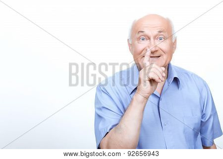 Old man holding finger in front of the mouth