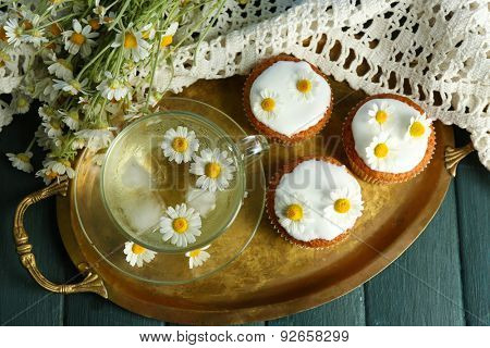 Cup of chamomile tea with chamomile flowers and tasty muffins on tray, on color wooden background
