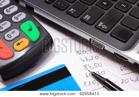 Payment Terminal With Credit Card, Laptop And Financial Calculations