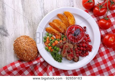Beef with cranberry sauce, roasted potato slices, vegetables and bun on plate, on color wooden background