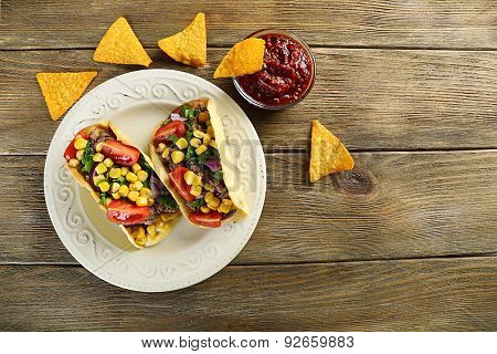 Mexican food Taco in plate on wooden table, top view