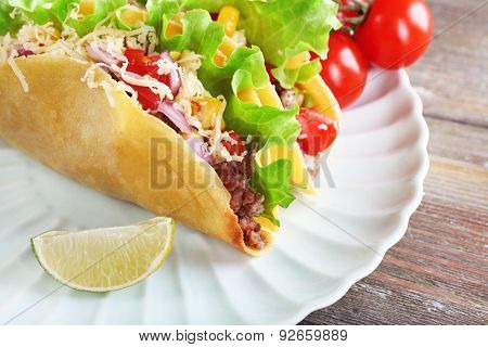 Tasty taco with vegetables on plate on table close up