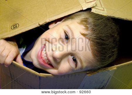 Child Peeking Out Of A Box