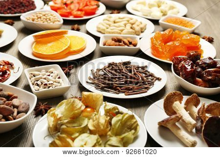 Different products on saucers on wooden table, closeup