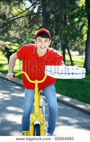 Young man delivering pizza box on bike outdoors