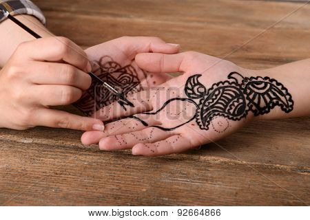 Process of applying Mehndi on female hand close up
