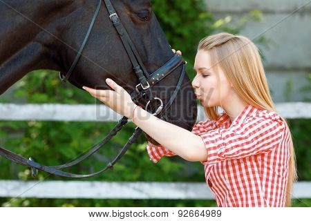 Vivacious young girl kissing the horse