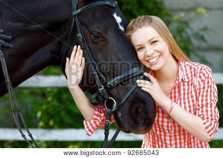 Smiling girl embracing the horse