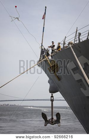 STATEN ISLAND, NY - MAY 20 2015: Linesmen work on the bow of USS Barry (DDG 52) guided-missile destroyer mooring for Fleet Week NY at Sullivans Pier with the Verrazano-Narrows Bridge in background.