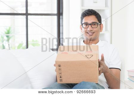 Courier delivery concept. Indian guy received an express parcel and checking the box at home. Asian man sitting on sofa indoor.