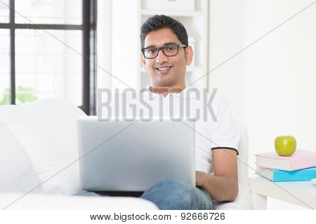 Indian guy with laptop computer working from home. Asian man using internet indoor, relaxed and sitting on sofa. Handsome male model.