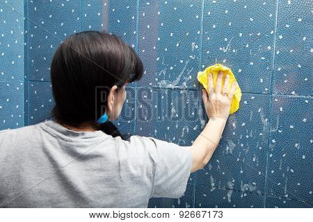 Woman Washes Tile With A Cloth
