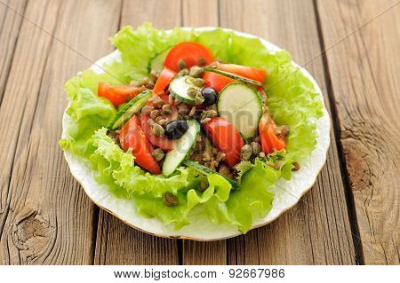 Lentil Salad With Fresh Tomatoes, Cucumbers, Capers And Lettuce On Wooden Table