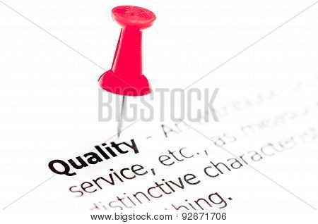 Word Quality Pinned On White Paper With Red Pushpin