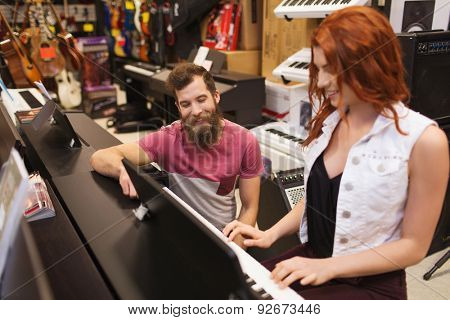 music, sale, people, musical instruments and entertainment concept - happy man and woman playing piano at music store