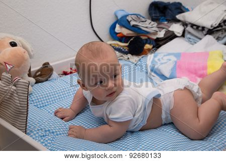 Cheerful Newborn Playing On The Diaper Table