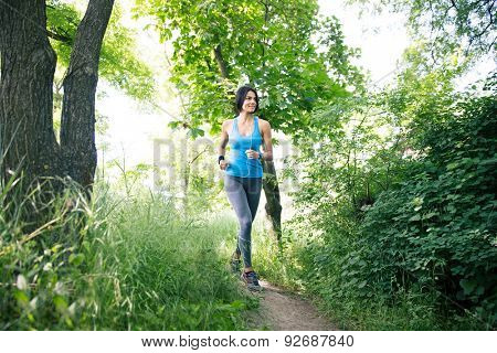Full length portrait of a young smiling sporty woman running outdoors in park. Looking away