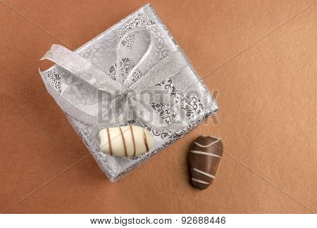 A small silver gift box with date chocolates. View from the top.